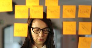 Η νέα επιχειρησιακή γυναίκα με τα γυαλιά κολλά τις μικρές αυτοκόλλητες ετικέττες στο γυαλί στο γραφείο απόθεμα βίντεο