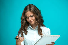 Η νέα επιχειρησιακή γυναίκα με τη μάνδρα και η ταμπλέτα για τις σημειώσεις για το μπλε υπόβαθρο Στοκ Εικόνα