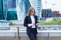 Η νέα επιχειρησιακή γυναίκα με τον καφέ αντιστοιχεί με τον πελάτη στο τηλέφωνο στην οδό Στοκ Φωτογραφία