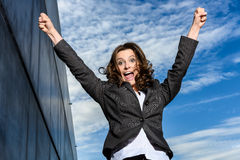 Η νέα επιχειρησιακή γυναίκα πηδά για τη χαρά μπροστά από τον μπλε νεφελώδη ουρανό Στοκ Φωτογραφία