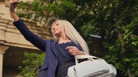 Η νέα επιχειρησιακή γυναίκα σε ένα κοστούμι ακούει τη μουσική και παίρνει ένα selfie στο smartphone της όμορφος ξανθός στηρίζεται φιλμ μικρού μήκους
