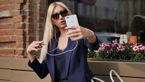 Η νέα επιχειρησιακή γυναίκα σε ένα κοστούμι ακούει τη μουσική και παίρνει ένα selfie στο smartphone της όμορφος ξανθός στηρίζεται απόθεμα βίντεο
