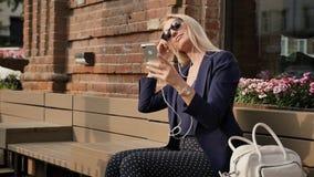 Η νέα επιχειρησιακή γυναίκα σε ένα κοστούμι ακούει τη μουσική στο smartphone της Όμορφος ξανθός στηρίζεται σε έναν πάγκο και μια  απόθεμα βίντεο