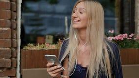 Η νέα επιχειρησιακή γυναίκα σε ένα κοστούμι γράφει ένα μήνυμα στο smartphone της Όμορφος ξανθός στηρίζεται σε έναν πάγκο και χρησ φιλμ μικρού μήκους