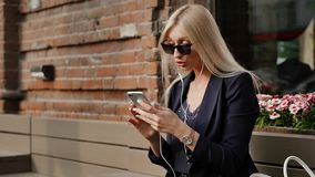 Η νέα επιχειρησιακή γυναίκα σε ένα κοστούμι γράφει ένα μήνυμα στο smartphone της Όμορφος ξανθός στηρίζεται σε έναν πάγκο και χρησ απόθεμα βίντεο
