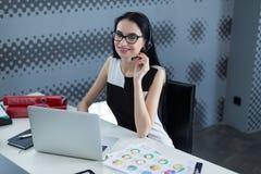 Η νέα επιχειρησιακή γυναίκα σε μια κάσκα εργάζεται σε ένα lap-top στο γραφείο Στοκ φωτογραφία με δικαίωμα ελεύθερης χρήσης