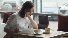 Η νέα επιχειρησιακή γυναίκα στηρίζεται κατά τη διάρκεια ενός μεσημεριανού διαλείμματος σε έναν καφέ και βγάζει φύλλα μέσω του περ Στοκ Εικόνες