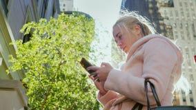 Η νέα επιχειρησιακή γυναίκα χρησιμοποιεί ένα smartphone σε μια μεγάλη πόλη Στα πλαίσια του αστικού τοπίου, ουρανοξύστες _ φιλμ μικρού μήκους