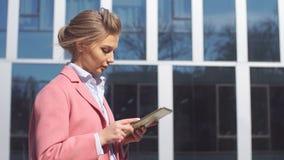 Η νέα επιχειρησιακή γυναίκα χρησιμοποιεί μια ταμπλέτα στο υπόβαθρο του κτιρίου γραφείων φιλμ μικρού μήκους