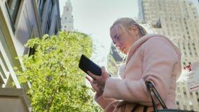 Η νέα επιχειρησιακή γυναίκα χρησιμοποιεί μια ταμπλέτα σε μια μεγάλη πόλη Στα πλαίσια του αστικού τοπίου, ουρανοξύστες Ο ήλιος απόθεμα βίντεο