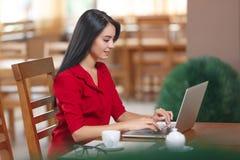 Η νέα επιχειρησιακή γυναίκα χρησιμοποιεί το lap-top στον καφέ Στοκ Φωτογραφίες