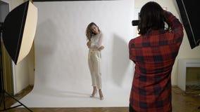 Η νέα εργασία φωτογράφων σε ένα επαγγελματικό στούντιο που παίρνει τις εικόνες ενός ξανθού κοριτσιού με τη σγουρή τρίχα έντυσε στ απόθεμα βίντεο