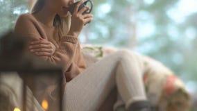 Η νέα ευτυχής γυναίκα απολαμβάνει του φλυτζανιού του καυτού σπιτιού συνεδρίασης καφέ από το μεγάλο παράθυρο με το υπόβαθρο δέντρω απόθεμα βίντεο