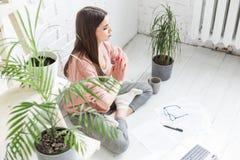 Η νέα ευτυχής γυναίκα κάθεται στο πάτωμα σε μια γιόγκα θέτει σε ένα φωτεινές διαμέρισμα και μια εργασία πίσω από ένα lap-top, ένα στοκ φωτογραφία με δικαίωμα ελεύθερης χρήσης