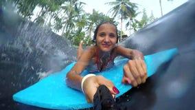 Η νέα ευτυχής γυναίκα κρατά πηγαίνει υπέρ άλματα καμερών δράσης στη λίμνη στη μύγα ολίσθησης Ν έλξης Koh Phangan νησιών μέσα απόθεμα βίντεο