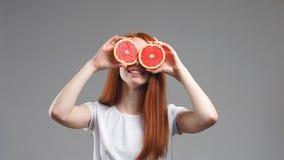 Η νέα ευτυχής γυναίκα κρατά τις φέτες των γκρέιπφρουτ στα μάτια της στο άσπρο υπόβαθρο απόθεμα βίντεο