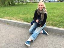 Η νέα ευτυχής γυναίκα με μια μεγάλη κάμερα καθρεφτών κάθεται στο χορτοτάπητα από το δρόμο στοκ εικόνα με δικαίωμα ελεύθερης χρήσης