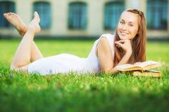 Η νέα ευτυχής γυναίκα σπουδαστών με το βιβλίο στα χέρια της βρίσκεται στοκ εικόνα