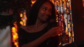 Η νέα ευτυχής γυναίκα στέκεται δίπλα στην προθήκη, χαμογελά και αγγίζει τη γιρλάντα στο υπόβαθρο των φω'των πόλεων απόθεμα βίντεο