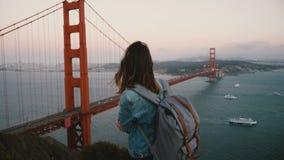 Η νέα ευτυχής γυναίκα τουριστών με το σακίδιο πλάτης περπατά το μεγαλοπρεπές τοπίο προσοχής της εικονικής χρυσής άποψης γεφυρών π απόθεμα βίντεο