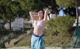 Η νέα ευτυχής γυναίκα χαλαρώνει και αναπνέει στην παραλία στοκ εικόνες
