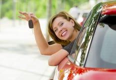 Η νέα ευτυχής ελκυστική γυναίκα που χαμογελά την υπερήφανη συνεδρίαση στην εκμετάλλευση θέσεων του οδηγού και που παρουσιάζει κλε στοκ εικόνα με δικαίωμα ελεύθερης χρήσης
