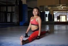 Η νέα ευτυχής και ιδρωμένη ασιατική γυναίκα στον αθλητισμό ντύνει το τέντωμα και να χωρίσει τα πόδια για τους μυς χαλάρωσης στο d Στοκ φωτογραφία με δικαίωμα ελεύθερης χρήσης