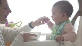 Η νέα ευτυχής μητέρα διδάσκει το μικρό παιδί μωρών της για να φάει από μόνη της από το κουτάλι, παιδικές τροφές απόθεμα βίντεο
