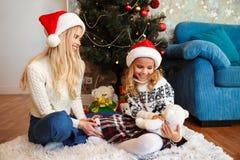 Η νέα ευτυχής μητέρα με την κόρη της που κρατά teddy αντέχει ενώ Si Στοκ φωτογραφίες με δικαίωμα ελεύθερης χρήσης