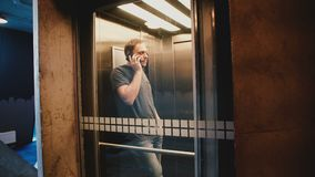 Η νέα ευτυχής οδήγηση επιχειρηματιών κάτω σε έναν διαφανή ανελκυστήρα γυαλιού που μιλά στο τηλέφωνο, πόρτα ανοίγει και περπατά έξ φιλμ μικρού μήκους