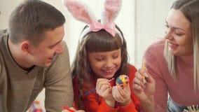Η νέα ευτυχής οικογένεια διακοσμεί μαζί ένα αυγό Πάσχας, το οποίο κρατά μια κόρη απόθεμα βίντεο