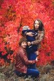 Η νέα ευτυχής οικογένεια, που καλύπτεται στο κάλυμμα, στέκεται κοντά στα όμορφα κόκκινα δέντρα φθινοπώρου στοκ εικόνα με δικαίωμα ελεύθερης χρήσης