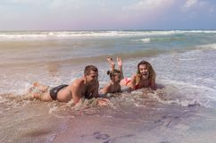 Η νέα ευτυχής οικογένεια mom, ο μπαμπάς και η κόρη παίζουν και λούζουν στη θάλασσα κατά τη διάρκεια των καλοκαιρινών διακοπών στοκ εικόνα με δικαίωμα ελεύθερης χρήσης