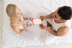 Η νέα ευτυχής συνεδρίαση ζεύγους στο κρεβάτι, ισπανικός άνδρας δίνει στην έκπληξη γυναικών τον παρόντα φάκελο με την κορδέλλα, επ Στοκ Φωτογραφία