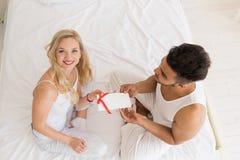 Η νέα ευτυχής συνεδρίαση ζεύγους στο κρεβάτι, ισπανικός άνδρας δίνει στην έκπληξη γυναικών τον παρόντα φάκελο με την κορδέλλα, επ Στοκ Φωτογραφίες