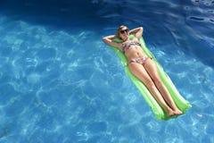 Η νέα ευτυχής όμορφη γυναίκα στο μπικίνι και τα γυαλιά ηλίου που βρίσκονται χαλαρώνουν στο επιπλέον σώμα στην πισίνα θερέτρου ξεν Στοκ Εικόνες