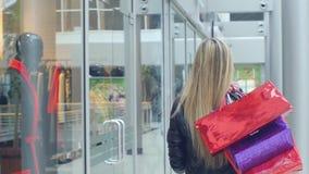 Η νέα ευτυχής όμορφη ξανθή γυναίκα πηγαίνει στις αγορές φιλμ μικρού μήκους