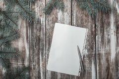 Η νέα ευχετήρια κάρτα έτους ` s στο παλαιό ξύλινο υπόβαθρο, με το πράσινο έλατο διακλαδίζεται, και άσπρο φύλλο για ένα συγχαρητήρ Στοκ Εικόνες