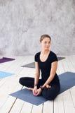 Η νέα ελκυστική γιόγκα άσκησης γυναικών, που κάθεται στην άσκηση Ardha Padmasana, μισό Lotus θέτει, επίλυση, φορώντας το Μαύρο Στοκ Εικόνα