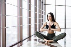 Η νέα ελκυστική γιόγκα άσκησης γυναικών χαμόγελου, που κάθεται στη μισή άσκηση Lotus, Ardha Padmasana θέτει Στοκ εικόνες με δικαίωμα ελεύθερης χρήσης