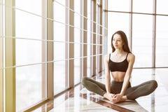 Η νέα ελκυστική γιόγκα άσκησης γυναικών χαμόγελου, που κάθεται στη μισή άσκηση Lotus, Ardha Padmasana θέτει Στοκ φωτογραφίες με δικαίωμα ελεύθερης χρήσης