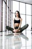 Η νέα ελκυστική γιόγκα άσκησης γυναικών χαμόγελου, που κάθεται στη μισή άσκηση Lotus, Ardha Padmasana θέτει Στοκ εικόνα με δικαίωμα ελεύθερης χρήσης