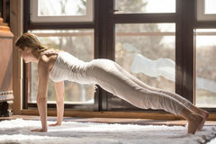 Η νέα ελκυστική γυναίκα γιόγκη στη σανίδα θέτει, εγχώριο εσωτερικό backgro Στοκ Φωτογραφίες