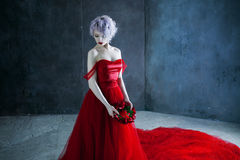 Η νέα θαυμάσια γυναίκα στο κόκκινο φόρεμα κρατά ένα στεφάνι των τριαντάφυλλων ανασκόπηση κατασκευασμένη Στοκ φωτογραφία με δικαίωμα ελεύθερης χρήσης
