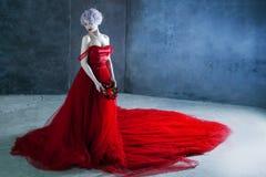 Η νέα θαυμάσια γυναίκα στο κόκκινο φόρεμα κρατά ένα στεφάνι των τριαντάφυλλων ανασκόπηση κατασκευασμένη Στοκ εικόνες με δικαίωμα ελεύθερης χρήσης
