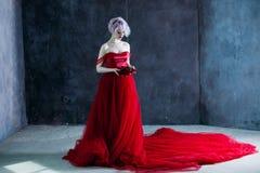 Η νέα θαυμάσια γυναίκα στο κόκκινο φόρεμα κρατά ένα στεφάνι των τριαντάφυλλων ανασκόπηση κατασκευασμένη Στοκ Εικόνες