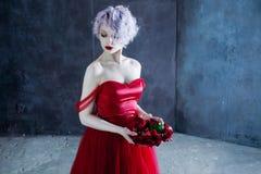 Η νέα θαυμάσια γυναίκα στο κόκκινο φόρεμα κρατά ένα στεφάνι των τριαντάφυλλων ανασκόπηση κατασκευασμένη Στοκ Φωτογραφίες