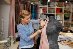 Η νέα θηλυκή μοδίστρα συνδέει το ύφασμα με το μανεκέν χρησιμοποιώντας τις βελόνες δημιουργία του σχεδίου φορεμάτων στο εργαστήριο στοκ φωτογραφία με δικαίωμα ελεύθερης χρήσης