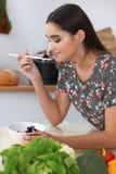 Η νέα ισπανική γυναίκα μαγειρεύει στην κουζίνα Η νοικοκυρά δοκιμάζει τη φρέσκια σαλάτα καθμένος στον πίνακα Στοκ Εικόνες