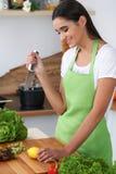 Η νέα ισπανική γυναίκα μαγειρεύει στην κουζίνα Η νοικοκυρά κόβει τα λαχανικά και το πράσινο κρέας για τη φρέσκια σαλάτα Ισπανός Στοκ Φωτογραφία